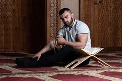 Привлекательные мусульмане Гай читая Koran стоковые фото