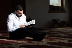 Привлекательные мусульмане Гай читая Koran стоковое изображение