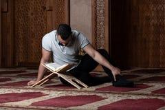 Привлекательные мусульмане Гай читая Koran стоковые изображения