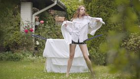 Привлекательные ноги танцев и поднимать молодой женщины на дворе пока делающ домашнее хозяйство с полотенцем в руках Активный видеоматериал
