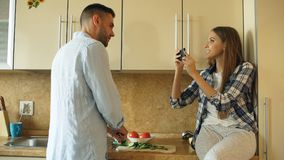 Привлекательные пары варя в кухне и принимая фото используя smartphone fo деля социальные средства массовой информации дома стоковое фото