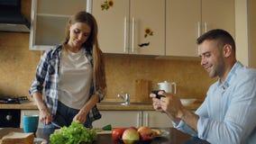 Привлекательные пары в кухне Укомплектуйте личным составом играть видеоигру на smartphone пока его варить подруги Стоковая Фотография