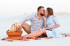 Привлекательные пары сидя совместно на пляже с белым песком, молодой паре целуя на пляже, счастливых парах наслаждаясь пикником н Стоковое Изображение