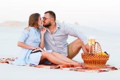 Привлекательные пары сидя совместно на пляже с белым песком, youn Стоковая Фотография RF