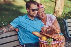 Привлекательные пары среднего возраста во время датировка, наслаждаясь пикником на стенде в парке города стоковое изображение