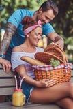 Привлекательные пары среднего возраста во время датировка, наслаждаясь пикником на стенде в парке города стоковое фото rf