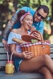 Привлекательные пары среднего возраста во время датировка, наслаждаясь пикником на стенде в парке города стоковая фотография rf