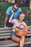 Привлекательные пары среднего возраста во время датировка, наслаждаясь пикником на стенде в парке города стоковое изображение rf