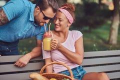 Привлекательные пары среднего возраста во время датировка, наслаждаясь пикником на стенде в парке города стоковые изображения rf