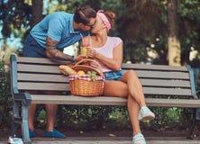 Привлекательные пары среднего возраста во время датировка, наслаждаясь пикником на стенде в парке города стоковые изображения