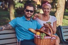Привлекательные пары среднего возраста во время датировка, наслаждаясь пикником на стенде в парке города стоковое фото