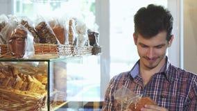 Привлекательные печенья молодого человека покупая на хлебопекарне видеоматериал