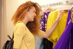 Привлекательные покупки молодой женщины для одежд в магазине стоковое фото
