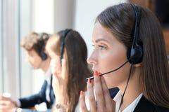 Привлекательные положительные молодые предприниматели и коллеги в офисе центра телефонного обслуживания Стоковые Фотографии RF
