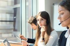 Привлекательные положительные молодые предприниматели и коллеги в офисе центра телефонного обслуживания Стоковые Изображения