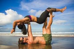 Привлекательные портрета образа жизни Outdoors молодые и сконцентрированные пары акробатов йоги практикуя баланс и раздумье acroy стоковые фотографии rf