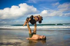 Привлекательные портрета образа жизни Outdoors молодые и сконцентрированные пары акробатов йоги практикуя баланс и раздумье acroy стоковые изображения rf