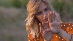 Привлекательные руки молодой женщины с золотыми яркими блесками в поле на заходе солнца движение медленное сток-видео
