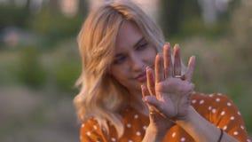 Привлекательные руки молодой женщины с золотыми яркими блесками в поле на заходе солнца движение медленное видеоматериал