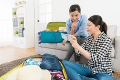 Привлекательные сестры пакуя багаж в живущей комнате Стоковое Изображение RF