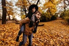 Привлекательные счастливые роскошные пары имея потеху и смеясь над в осени Стоковая Фотография