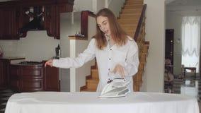 Привлекательные танцы молодой женщины пока делающ домашнее хозяйство дома Активная положительная домохозяйка утюжа ее одежды на у видеоматериал