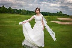 Привлекательные танцы невесты на зеленом поле для гольфа Стоковое Изображение RF