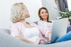 привлекательные усмехаясь девушки используя компьтер-книжку Стоковые Фотографии RF