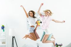 привлекательные excited девушки скача с подушками Стоковые Изображения