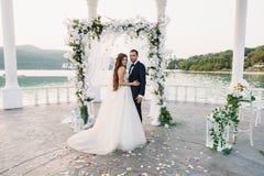 Привлекательные groom и невеста на дне свадьбы ceremory с сводом и озером на предпосылке стоят совместно Красивые новобрачные Стоковое Изображение RF