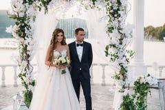 Привлекательные groom и невеста на дне свадьбы ceremory с сводом и озером на предпосылке стоят совместно Красивые новобрачные Стоковое фото RF