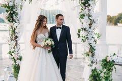 Привлекательные groom и невеста на дне свадьбы ceremory с сводом и озером на предпосылке стоят совместно Красивые новобрачные Стоковая Фотография RF