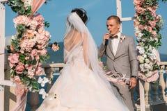 Привлекательные groom и невеста на дне свадьбы ceremory с сводом и озером на предпосылке стоят совместно Красивые новобрачные Стоковое Изображение
