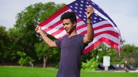 Привлекательный Афро-американский человек держа американский флаг в его руках на заднем положении в зеленом поле после этого подн