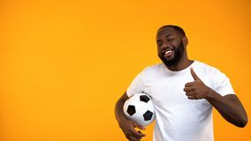Привлекательный Афро-американский человек держа футбольный мяч и показывая большие пальцы руки вверх по знаку стоковые изображения rf