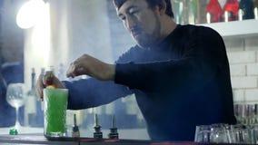 Привлекательный бармен украшает с клубниками и апельсином спиртной коктеиль в стекле на таблице бара сток-видео
