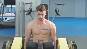 Привлекательный без рубашки белокурый мужской культурист в шортах внутри помещения в темном спортзале, показывая мышечный торс и  акции видеоматериалы