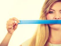 Привлекательный белокурый рот заволакивания женщины с лентой Стоковые Изображения