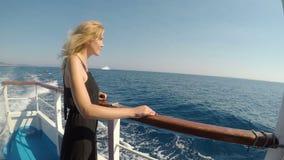 Привлекательный белокурый турист женщины на шлюпке наблюдая море наслаждаясь ветерком на летний день каникул - сток-видео