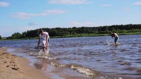Привлекательный белый мужчина в скольжениях футболки на доске воды на крае влажного пляжа песка акции видеоматериалы