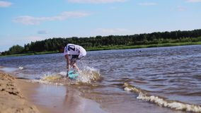 Привлекательный белый парень в скольжениях футболки на доске воды на крае влажного пляжа песка видеоматериал