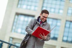 Привлекательный бизнесмен держа документы, бумаги стоковые фотографии rf