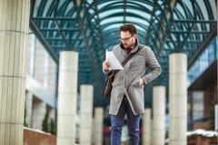 Привлекательный бизнесмен держа документы, бумаги стоковые изображения