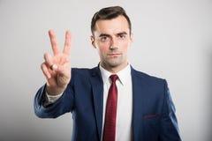 Привлекательный бизнесмен показывая жест номер два стоковые фотографии rf