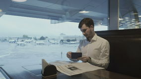 Привлекательный бизнесмен смотрит его посадочный талон в авиапорте видеоматериал