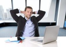 Привлекательный бизнесмен счастливый на конторской работе сидя на удовлетворяемом столе компьютера и ослабленном усмехаться Стоковое Изображение