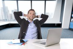 Привлекательный бизнесмен счастливый на конторской работе сидя на удовлетворяемом столе компьютера и ослабленном усмехаться Стоковое фото RF