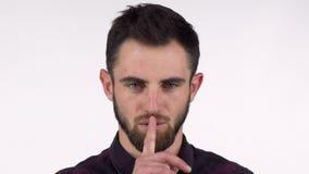 Привлекательный бородатый человек shushing к камере с пальцем к его губам видеоматериал