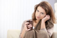 привлекательный выпивая чай софы девушки сидя Стоковые Изображения