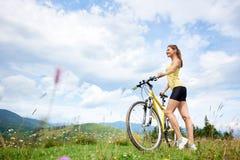 Привлекательный женский велосипедист при желтый велосипед горы, наслаждаясь солнечным днем в горах стоковая фотография rf